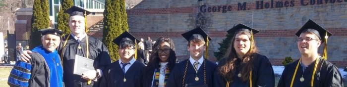 group of graduates and faculty in graduation regalia