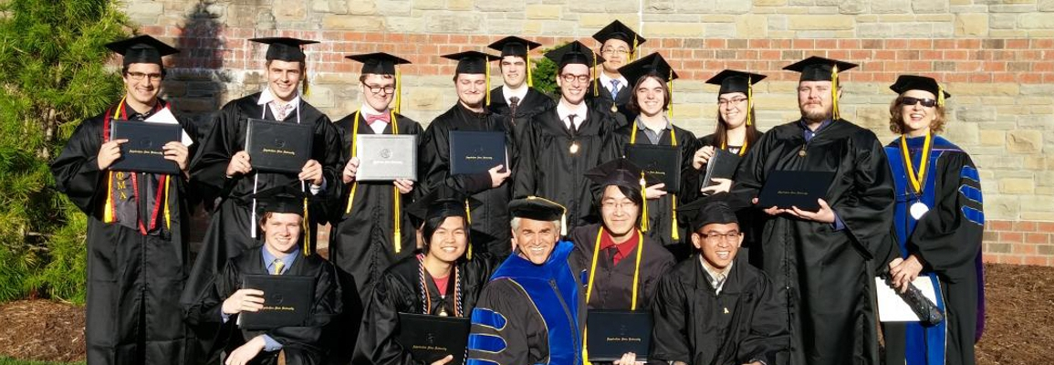 Spring 2016 graduates and faculty in regalia outside Holmes Convocation Center